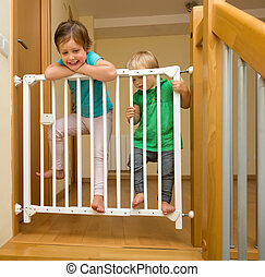 Two girls approaching safety gate of stairs - Two baby girls...