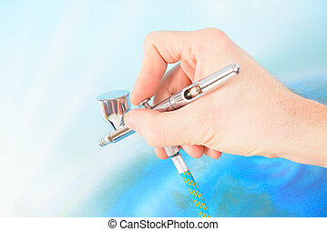 Airbrush - Hand holding a professional airbrush over...