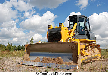Bulldozer is stnading in the field against the blue sky and...