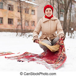 woman in red cap cleans carpet with snow - Smiling woman in...