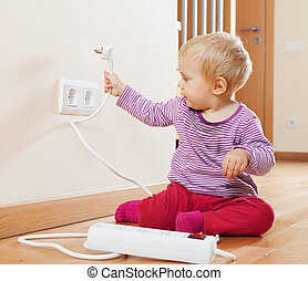Toddler playing with electrical extension and outlet on...