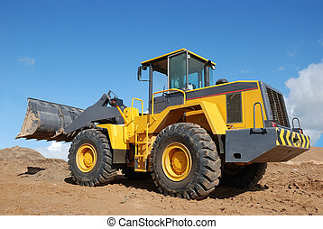 Wheel loader bulldozer with bucket outdoors over blue sky