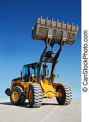 wheel loader with fully raised bucket over blue sky