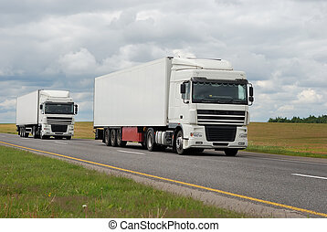 couple of white trucks on highway
