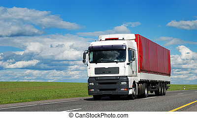 white lorry with red trailer on the highway over blue cloudy...