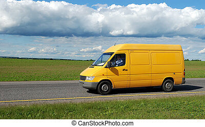 yellow delivery truck outdoor on the highway over blue...