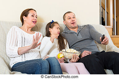 Family watching TV show - Parents and little daughter...