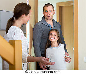 Couple with girl at doorway - Happy woman standing at...