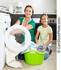Woman with daughter near washing machine - Home family...
