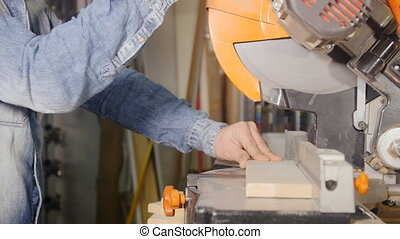 cutting wooden plank circular saw - sawing board wood in a...
