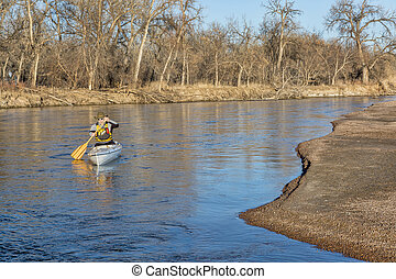 canoe paddling on South Platte RIver - senior paddler in a...