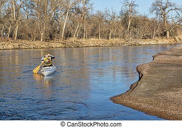 canoe paddling on South Platte RIver - senior paddler in a...