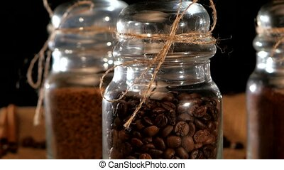 Delicious, roasted coffee beans in bottle on sacking, cam moves top down