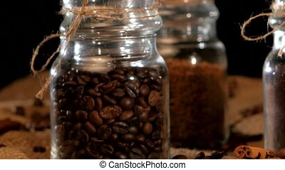 Roasted coffee beans in bottle on sacking, cam moves upwards...
