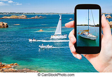 tourist taking photo of yacht near Brittany - travel concept...