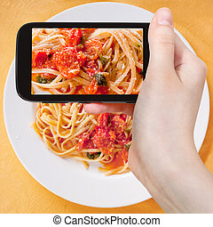 tourist taking photo spaghetti with tomato sauce