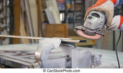 grinding metal with angle grinder - worker grinding a steel...