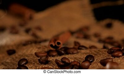 Coffee beans with cinnamon near the coffee bottle on black background, rotation