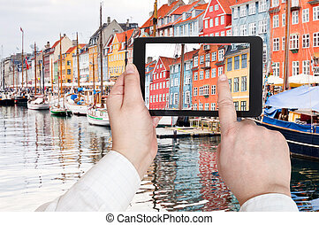 tourist taking photo of Nyhavn harbor district - travel...