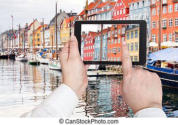 tourist taking photo of Nyhavn harbor district - travel...