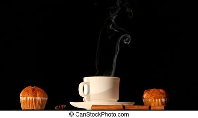White steaming coffee cup with cakes, anise, cinnamon on...