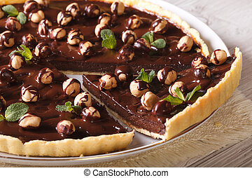 Cut the chocolate tart with hazelnut close-up, horizontal -...