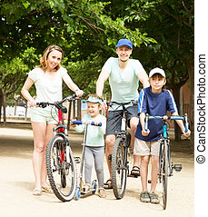Active happy family with bicycles in park
