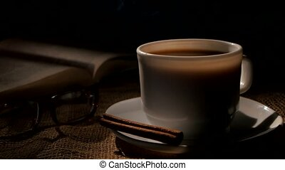 Hot coffee and book with glasses, cinnamon on sacking, black...