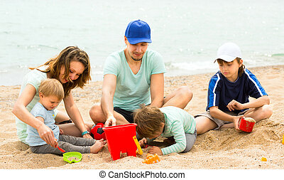 father and mother with  children at seaside