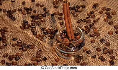 Bottle with coffee beans and cinnamon on sacking