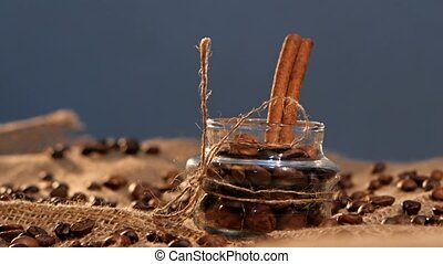 Little bottle with coffee beans and cinnamon on sacking, close up, gray background