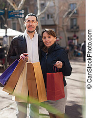 man and woman with purchases at street