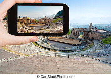 tourist taking photo of ancient amphitheater - travel...