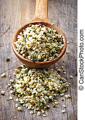 spoon of hemp seeds on old wooden table background