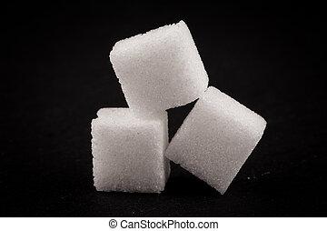 White refined sugar on dark stone background