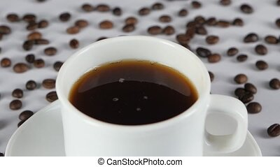 Pouring splashing coffee in cup, slow motion