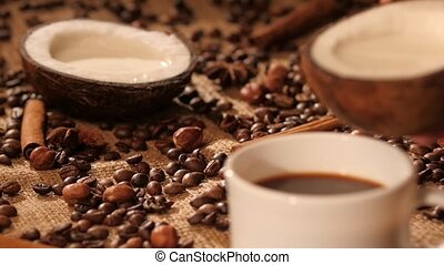 Pouring coconut milk into a cup with coffee, dynamic change of focus