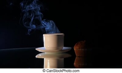 Hot coffee in white cup with cake on black background
