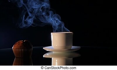 Hot coffee in white cup with cake isolated on black...