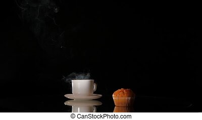 Cup of hot smoking coffee with cake on dark background -...
