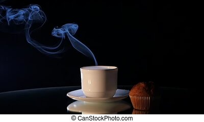 Cup of hot coffee with muffin on black background - White...