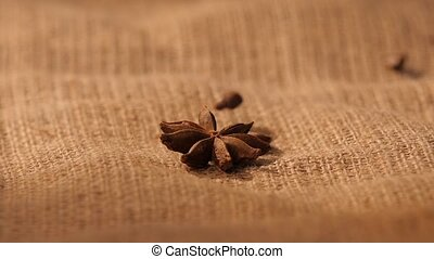 Anise, falling coffee beans on sacking, close up