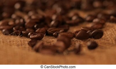 Falling brown coffee beans on sacking, close up