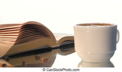 Cup of delicious coffee, milk with turning pages book...