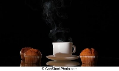 White cup of hot smoking coffee with muffins on dark...