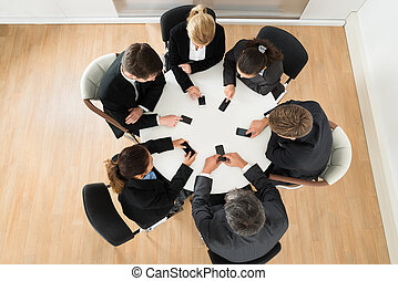 Businesspeople Using Cell Phone - Group Of Businesspeople...