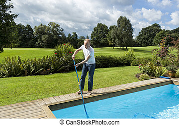 Man Cleaning Swimming Pool - Full Length of Man Cleaning...