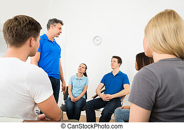 Man Explaining To His Friends - Group Of People Looking At...