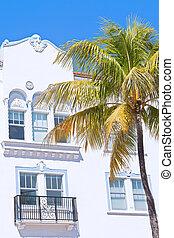Art deco architecture of Miami Beach, Florida. Beautiful building facade and tall coconut palm.