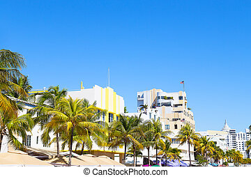 Modern buildings of Miami Beach, Florida. Street with art deco buildings, palms and colorful street umbrellas.